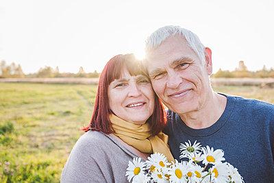 Smiling senior couple with chamomile flowers - p300m2225491 by Ekaterina Yakunina