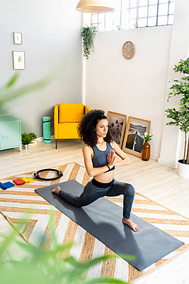 Woman in sports clothing doing sun salutation in living room - p300m2275429 by Giorgio Fochesato