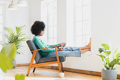 Young woman using mobile phone while sitting on armchair at home - p300m2276423 by Steve Brookland