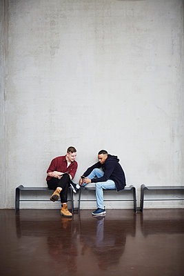 Full length of male friends with technologies sitting on bench against wall in university - p426m2022758 by Maskot