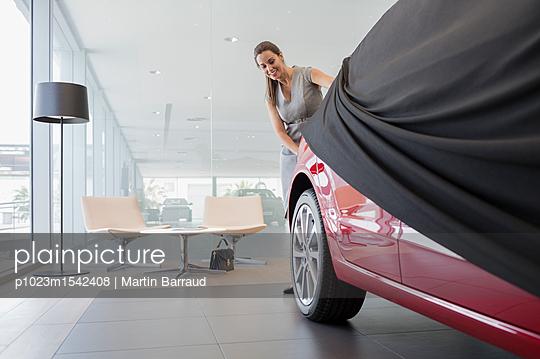 plainpicture | Photo library for authentic images - plainpicture p1023m1542408 - Car saleswoman removing cov... - plainpicture/Caiaimages/Martin Barraud