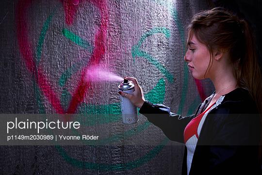Young woman spraying graffiti - p1149m2030989 by Yvonne Röder