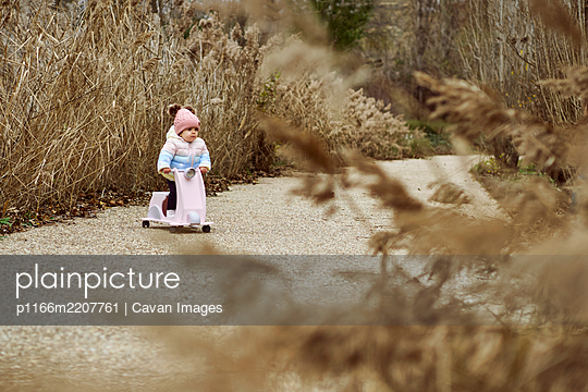 A 1 year old baby girl is with a pink motorcycle outside - p1166m2207761 by Cavan Images