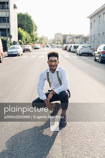 Portrait of a confident stylish young man crouching on the street in the city - p300m2202856 by Eugenio Marongiu