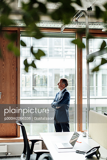 Businessman day dreaming while standing with arms crossed at glass window in office - p300m2266338 by Gustafsson