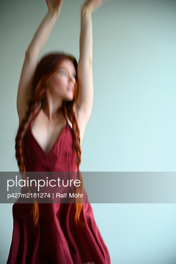 Red-haired woman with long pigtails in a dancing pose - p427m2181274 by Ralf Mohr