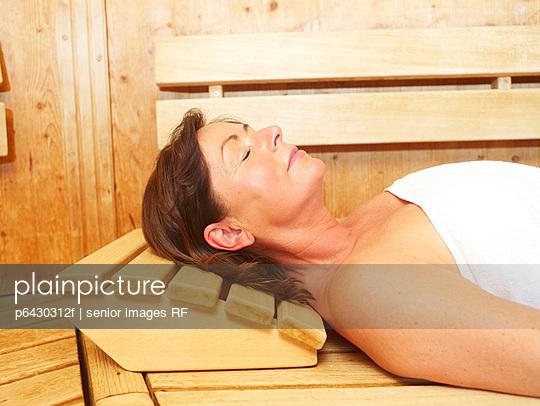 Aeltere Frau entspannt in der Sauna  - p6430312f von senior images RF