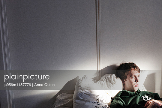 Young man laying on bed - p956m1137776 by Anna Quinn