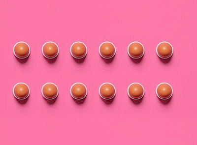 Overhead view of brown eggs in bowls arranged on pink background - p1166m2112232 by Cavan Images
