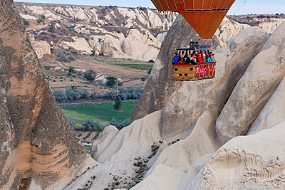 Turkey, Eastern Anatolia, Cappadocia, view to gondola of hot air balloon  hoovering over tuff rock formation at Goereme National Park - p300m949063 by Martin Siepmann