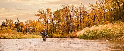 Caucasian man fishing in river - p555m1301785 by Mike Kemp