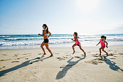 Mother and daughters running at beach - p555m1305537 by Peathegee Inc