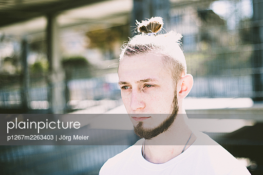 Young man with pigtail and chin beard - p1267m2263403 by Jörg Meier