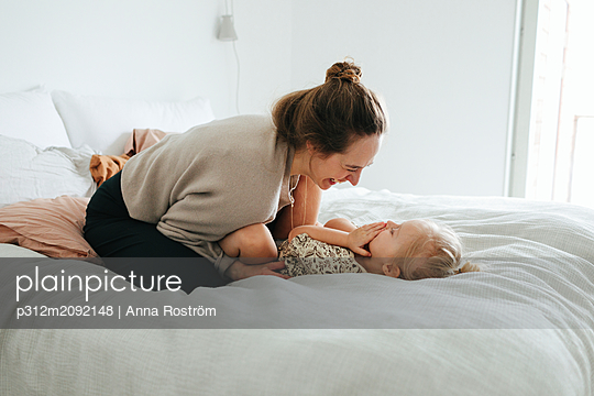 Mother playing with daughter on bed - p312m2092148 by Anna Roström