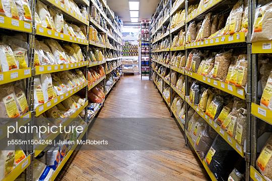 Bags of food in supermarket aisle - p555m1504248 by Julien McRoberts