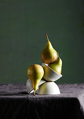 Pears and stacked dishes on a table - p1629m2211343 by martinameier
