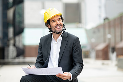 Thoughtful male architect in hardhat looking away while holding blueprint - p300m2275187 by Jose Carlos Ichiro