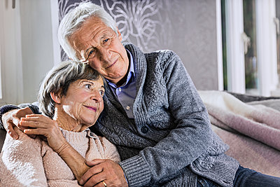 Senior man sitting with arm around on woman in living room - p300m2287229 by Stefanie Aumiller