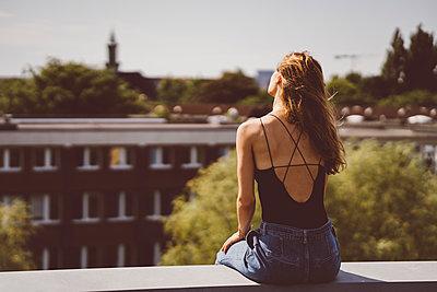 Junge Frau sitzt am Rand eines Hausdachs - p432m2231535 von mia takahara