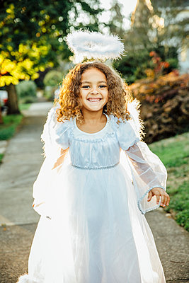 Mixed race girl wearing angel costume on sidewalk - p555m1412564 by Inti St Clair