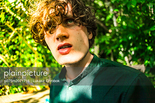 Young man with curly hair - p075m2071716 by Lukasz Chrobok