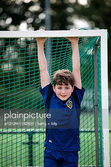Junge auf dem Sportplatz hängt im Tor - p1212m1152931 von harry + lidy