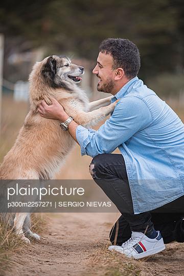 Smiling man embracing dog while kneeling on dirt road - p300m2257271 by SERGIO NIEVAS