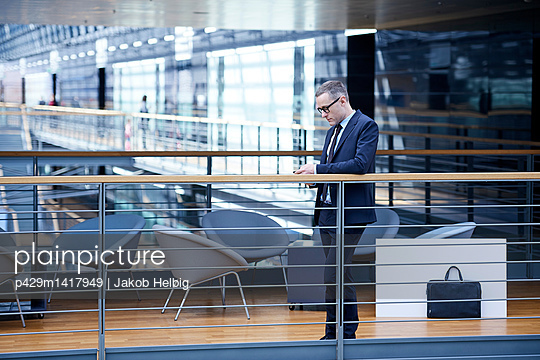 Businessman looking at smartphone on office balcony - p429m1417949 by Jakob Helbig