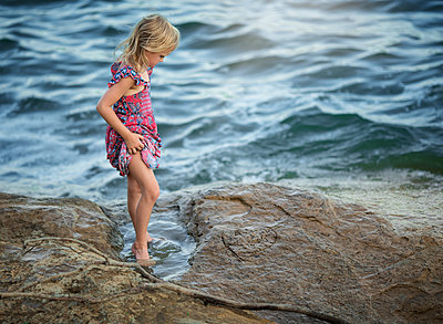 Full length of girl holding dress while standing in sea on shore - p1166m1547441 by Cavan Social