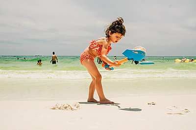 Portrait of young girl shoveling sand on beach - p1166m2094957 by Cavan Images