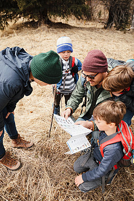 Family with guide map hiking in woods - p1192m2094165 by Hero Images