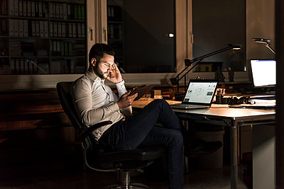 Businessman using tablet in office at night - p300m1581305 von Uwe Umstätter