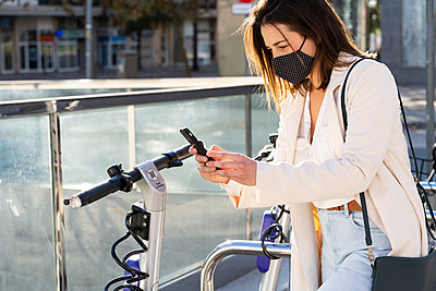 Young female entrepreneur doing contactless payment while standing at bicycle parking station - p300m2239919 by VITTA GALLERY