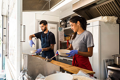Young multi-ethnic male and female colleagues preparing food in food truck - p426m2046489 by Maskot