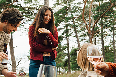 Cheerful woman talking with friends enjoying drinks in back yard - p426m2149234 by Maskot