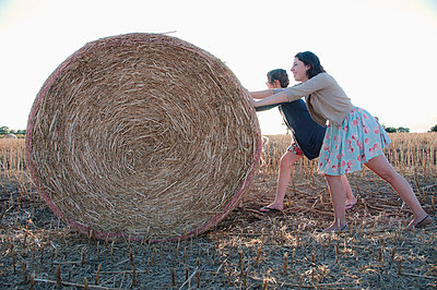 Girls pushing hay bale in field - p42916833f by Simon Potter