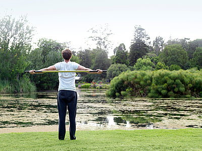 Rear view of young man in park practicing martial arts with a bo staff - p429m1407879 by Elke Meitzel