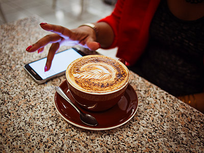 Mixed race woman using cell phone with coffee in cafe - p555m1411857 by Donald Iain Smith