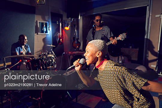 Female musician singing into microphone in recording studio - p1023m2190281 by Trevor Adeline