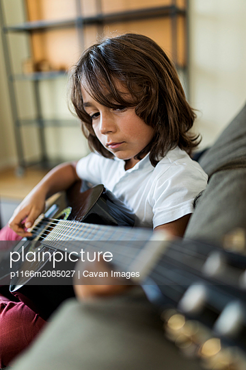 young boy practicing guitar sitting on the sofa at home - p1166m2085027 by Cavan Images