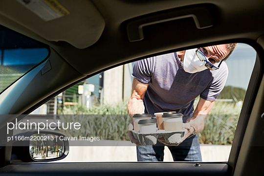 Take out coffee delivered to car window - p1166m2200213 by Cavan Images