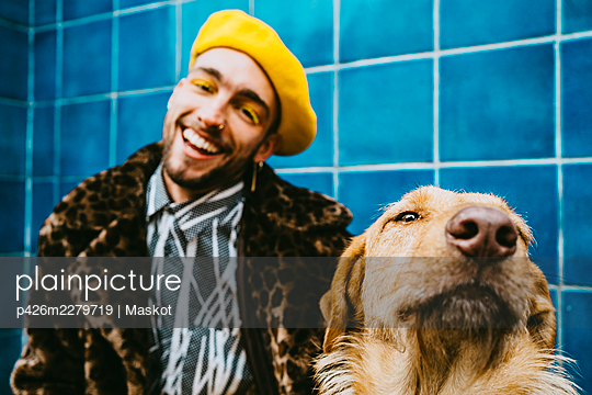Happy young man with Golden Retriever dog - p426m2279719 by Maskot