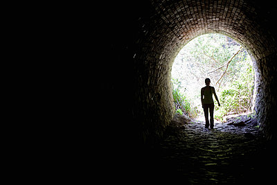 Woman standing in a tunnel opening - p1166m2171530 by Cavan Images
