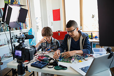 Boys videotaping circuit board assembly in bedroom - p1192m1129550f by Hero Images