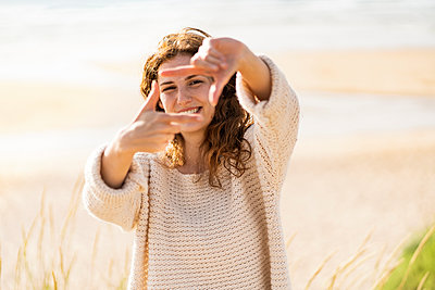 Happy woman looking through finger frame at beach during sunny day - p300m2286957 by Steve Brookland
