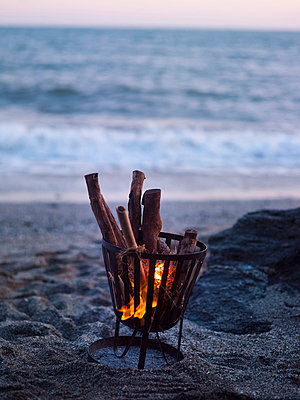 Fire in camping stove on beach at dusk - p312m714777 by Per Magnus Persson