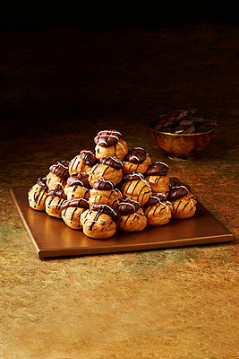 Still life with stacked chocolate profiteroles on gold plate, christmas dessert - p429m2068590 by Danielle Wood