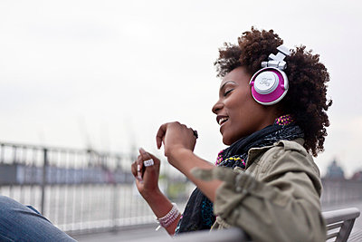 Woman listening to music - p6420227 by brophoto