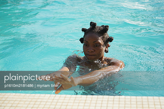 African woman in swimming pool - p1610m2181486 by myriam tirler