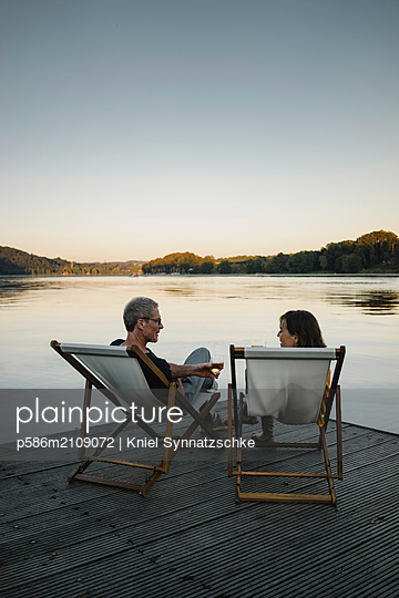 Mature couple drinking white whine at Lake Baldeneysee  - p586m2109072 by Kniel Synnatzschke